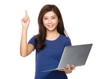 Young woman hold with laptop computer and finger pointing up Royalty Free Stock Images