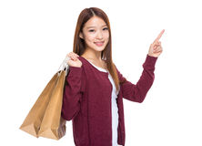 Young woman hold shopping bag and finger point up Royalty Free Stock Photo