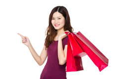 Young woman hold with shopping bag and finger point upwards Stock Photography