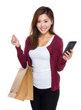 Young woman hold shopping bag and mobile phone Stock Photo