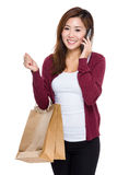Young woman hold shopping bag and talk to mobile Stock Images