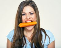 Young woman holdin carrot in teeth. Royalty Free Stock Photo