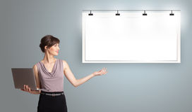 Free Young Woman Holding A Laptop  And Presenting Modern Copy Space Royalty Free Stock Photo - 50115705