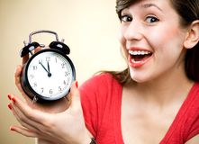 Young woman holding alarm clock Stock Image