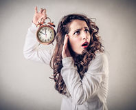 Young woman holding an alarm clock Royalty Free Stock Photos