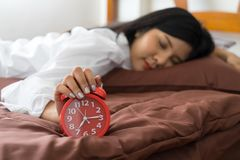 Young woman holding alarm clock on bed. wake up early in morning. Girl stop snooze alarm. female waking up sleepy and tired. woman wake up in the morning with stock photography
