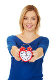 Young woman holding alarm clock. Royalty Free Stock Photography