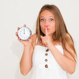 Young woman holding alarm clock and hushing Stock Photos