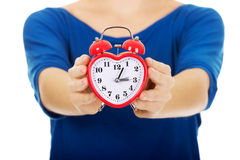 Young woman holding alarmclock. Royalty Free Stock Images