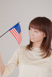 Young woman holding American Flag. Young woman looking at American Flag Royalty Free Stock Image
