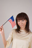 Young woman holding American Flag. Waist of of young Asian woman holding American Flag Royalty Free Stock Image