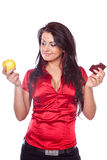 Young woman holding apple and chocolates Royalty Free Stock Photos