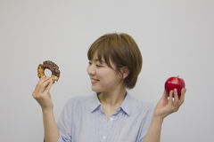 Young woman holding an apple and a doughnut Royalty Free Stock Photography