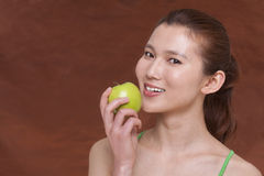 Young woman holding a apple and getting ready to take a bite, looking at camera, studio shot Royalty Free Stock Photos