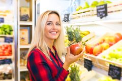 Young woman holding an apple in her hand at the food store. Young smiling attractive woman holding a fresh red apple in her hand at the food store Royalty Free Stock Image