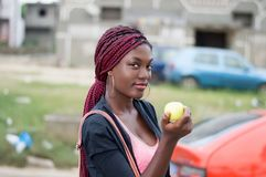 Young woman holding an apple looking at the camera. Royalty Free Stock Images