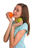 Young woman holding apple and orange over white Royalty Free Stock Image