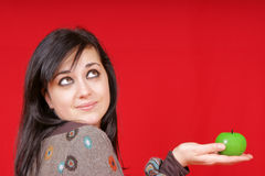 Young woman holding an apple-shaped candle. Portrait of a beautiful young woman holding a green apple-shaped candle. Studio shot over red background Stock Images