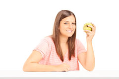 Young woman holding an apple and sitting at table Stock Photos
