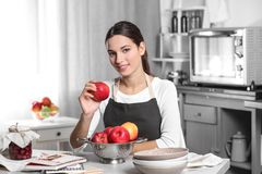Young woman holding apple and sitting. At kitchen table Stock Photo