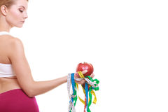 Young woman holding apple and tape measures. Royalty Free Stock Photos