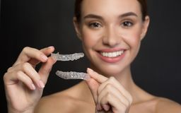 Young woman is holding artificial plastic jaw. Taking care of teeth. Close up of clear aligners in hands of happy girl who is standing and showing orthodontic stock photos