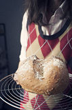 Young woman holding artisan bread. Young woman holding a round artisan bread Royalty Free Stock Photography