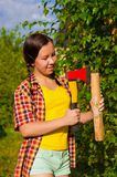Young woman holding an axe and chock Royalty Free Stock Photos