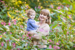 Young woman holding a baby girl in a garden. Young women holding a little baby girl in a garden on sunset Royalty Free Stock Images