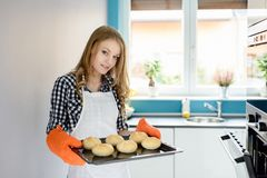Young woman holding a baking tray with bread rolls Royalty Free Stock Images