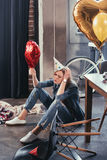 Young woman holding balloon in messy room after party Stock Photography