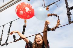 Young woman holding balloons having fun. Outdoors Stock Image