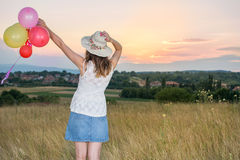 Young woman holding balloons looking at sunset. Young woman holding balloons and looking at sunset Royalty Free Stock Photography