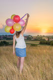 Young woman holding balloons looking at sunset. Young woman holding balloons and looking at sunset Stock Image