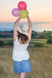Young woman holding balloons looking at sunset. Young woman holding balloons and looking at sunset Royalty Free Stock Photos