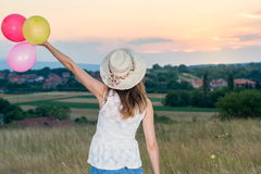 Young woman holding balloons looking at sunset. Young woman holding balloons and looking at sunset Stock Photo