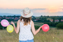 Young woman holding balloons looking at sunset. Young woman holding balloons and looking at sunset Royalty Free Stock Images