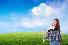 Young woman holding balloons on meadow summer. Young woman holding balloons on meadow summer with freedom lifestyle concept Royalty Free Stock Photos
