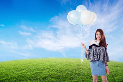 Young woman holding balloons on meadow summer with freedom lifestyle. Young woman holding balloons on meadow summer with freedom lifestyle concept Stock Image