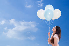 Young woman holding balloons on sky background. Young woman holding balloons on sky background lifestyle concept Royalty Free Stock Photography