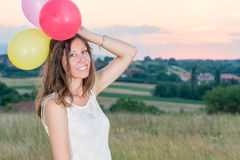 Young woman holding balloons at sunset. Young woman holding balloons at romantic sunset Royalty Free Stock Photo