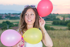 Young woman holding balloons at sunset. Young woman holding balloons at romantic sunset Royalty Free Stock Images