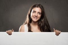 Woman holding a banner. Young woman holding a banner Royalty Free Stock Photography