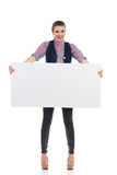 Young woman holding banner. An attractive young woman holding empty white placard. Full length studio shot isolated on white Stock Photos