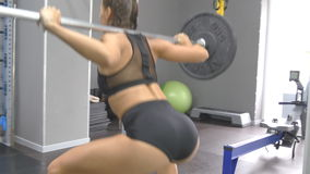 Young woman holding a barbell with heavy weights on her shoulders as she squats. Strong girl training in the gym stock footage