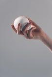 Young woman holding baseball ball on grey Royalty Free Stock Photography