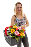Young woman is holding basket with bouquet of colorful flowers Royalty Free Stock Images