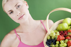 A young woman holding a basket of fruit, smiling Royalty Free Stock Photography