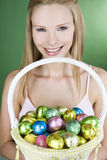 A young woman holding a basket full of Easter eggs, smiling Royalty Free Stock Photo