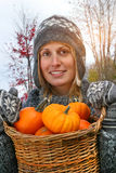 Young woman holding a basket full of pumpkins Royalty Free Stock Photos